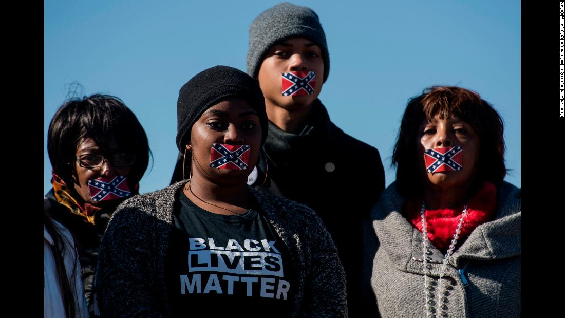 People in Jackson, Mississippi, protest in silence during the opening of the Mississippi Civil Rights Museum on Saturday, December 9. They were protesting against the Mississippi state flag, which still includes the Confederate battle flag in its upper-left corner.
