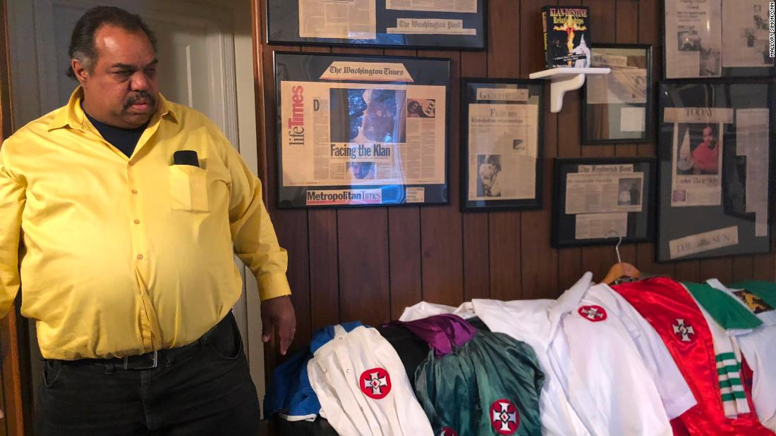 Daryl Davis looks at his collection of KKK robes, given up by Klansmen he has befriended.