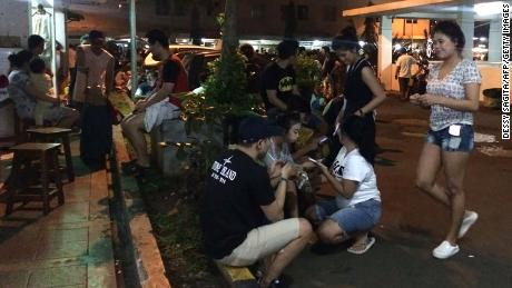 Residents gather outside their apartment blocks in Jakarta after the earthquake.