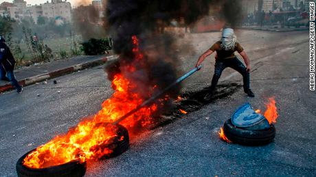 A Palestinian protester uses a stick to move flaming tires during clashes with Israeli forces on the outskirts of Ramallah on Friday.