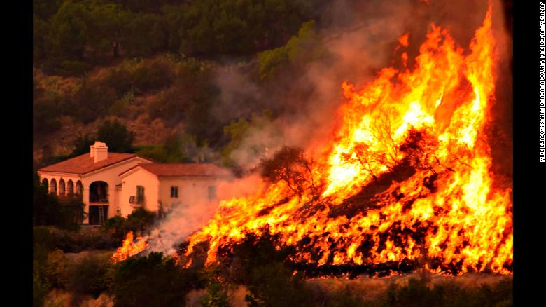 "Flames from a back-firing operation rise behind a home off Ladera Lane near Bella Vista Drive in Santa Barbara, California, on Thursday, December 14. Powerful Santa Ana winds and extremely dry conditions are fueling <a href=""http://www.cnn.com/2017/12/07/us/ventura-fire-california/index.html"" target=""_blank"">wildfires in Southern California</a> in what has been a devastating year for <a href=""http://www.cnn.com/interactive/2017/12/us/california-wildfires-cnnphotos/"" target=""_blank"">such natural disasters in the state.</a>"