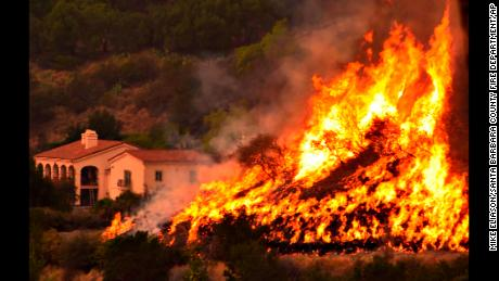In this Thursday, Dec. 14, 2017, photo provided by the Santa Barbara County Fire Department, flames from a back firing operation underway rise behind a home off Ladera Lane near Bella Vista Drive in Santa Barbara, Calif. Red Flag warnings for the critical combination of low humidity and strong winds expired for a swath of Southern California at midmorning but a new warning was scheduled to go into effect Saturday in the fire area due to the predicted return of winds. The so-called Thomas Fire, the fourth-largest in California history, was 35 percent contained after sweeping across more than 394 square miles (1,020 sq. kilometers) of Ventura and Santa Barbara counties since it erupted Dec. 4 a few miles from Thomas Aquinas College. (Mike Eliason/Santa Barbara County Fire Department via AP)