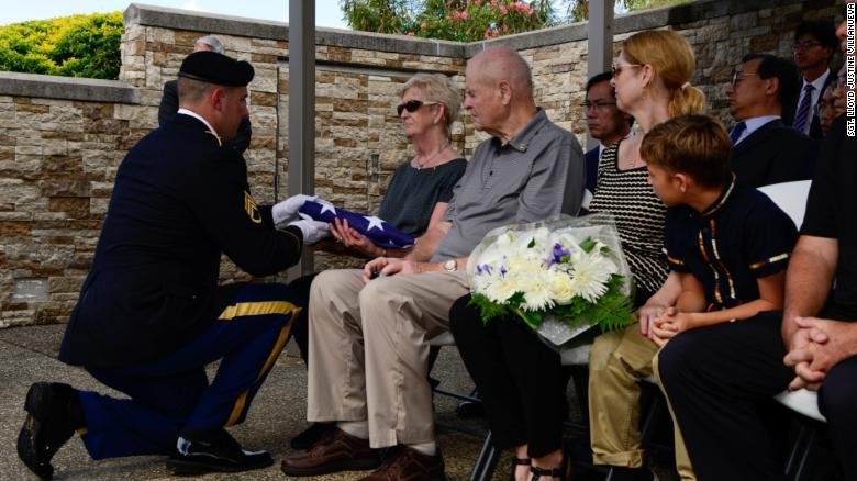 A soldier presents a burial flag to the next of kin of US Army Pfc. Albert E. Atkins on Friday at the National Memorial Cemetery of the Pacific in Honolulu, Hawaii.