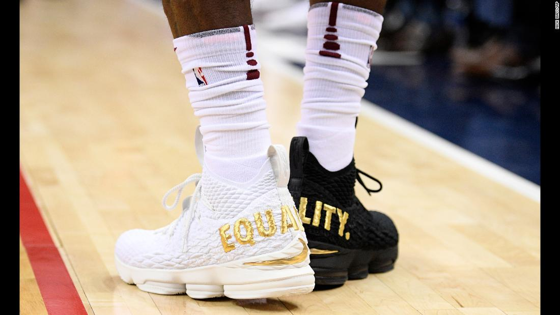 "Cleveland superstar LeBron James wears one white shoe and one black shoe during an NBA game in Washington on Sunday, December 17. <a href=""http://bleacherreport.com/articles/2749806-lebron-james-on-wearing-equality-shoes-not-going-to-let-1-person-dictate-us"" target=""_blank"">Read more on LeBron's statement about equality</a>"