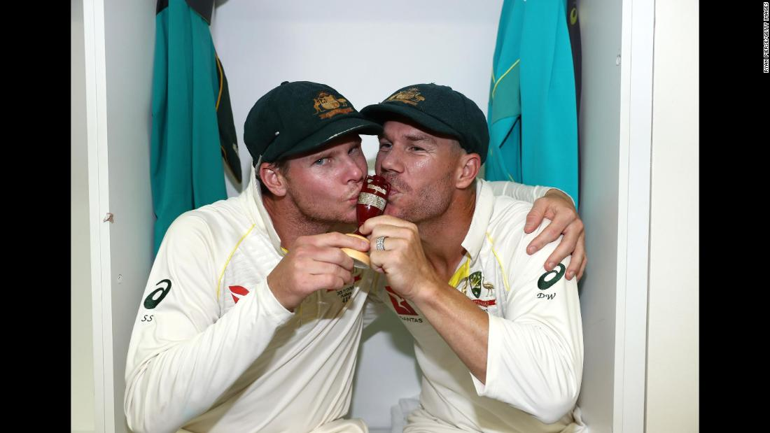 Australian cricketers Steve Smith, left, and David Warner celebrate with the Ashes urn after defeating England on Monday, December 18.