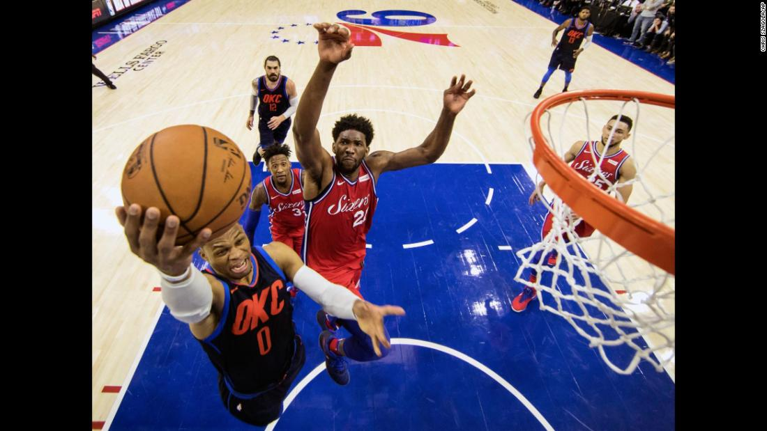 Oklahoma City's Russell Westbrook rises for a layup as Philadelphia's Joel Embiid looks for a block during an NBA game on Friday, December 15.