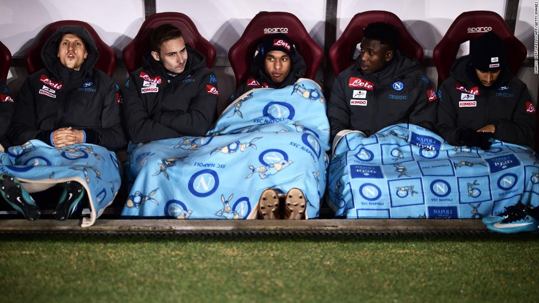 Napoli players cover themselves with blankets before a soccer match in Turin, Italy, on Saturday, December 16.