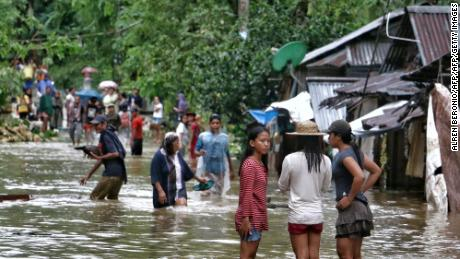TOPSHOT - Villagers wade through a flooded street in Brgy Calingatngan, in Borongan, on easterm Samar in central Philippines on December 16, 2017.  A boy drowned and tens of thousands were driven from their homes by floods as Tropical Storm Kai-Tak pounded the eastern Philippines, cutting off power and triggering landslides, officials said / AFP PHOTO / ALREN BERONIO        (Photo credit should read ALREN BERONIO/AFP/Getty Images)