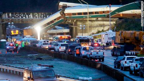 Traffic moves along northbound Interstate 5, left, as southbound lanes are filled with emergency vehicles near the scene of an Amtrak train crash Monday, Dec. 18, 2017, in DuPont, Wash. The Amtrak train making the first-ever run along a faster new route hurtled off the overpass Monday near Tacoma and spilled some of its cars onto the highway below, killing some people, authorities said. (AP Photo/Elaine Thompson)