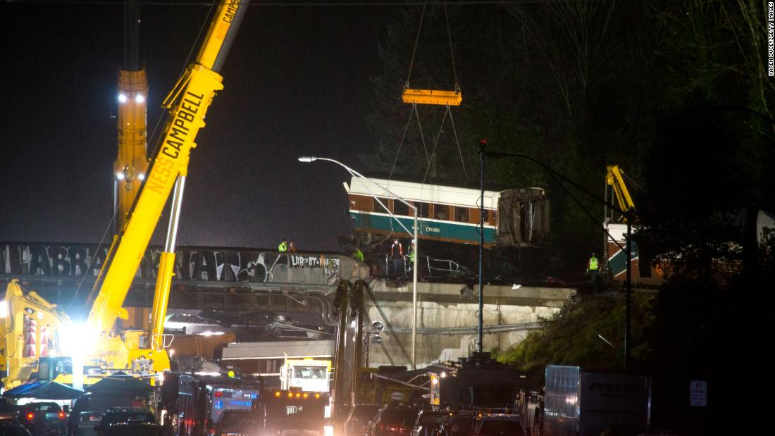 A train car is lifted away on Tuesday, December 19, the day after an Amtrak passenger train derailed near DuPont, Washington. Several of the train's cars spilled off an overpass and onto Interstate 5.