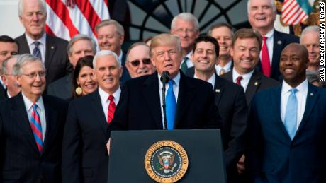 "US President Donald Trump flanked by Republican lawmakers speaks about the passage of tax reform legislation on the South Lawn of the White House in Washington, DC, December 20, 2017. Trump hailed a ""historic"" victory Wednesday as the US Congress passed a massive Republican tax cut plan, handing the president his first major legislative achievement since taking office nearly a year ago. / AFP PHOTO / SAUL LOEB        (Photo credit should read SAUL LOEB/AFP/Getty Images)"