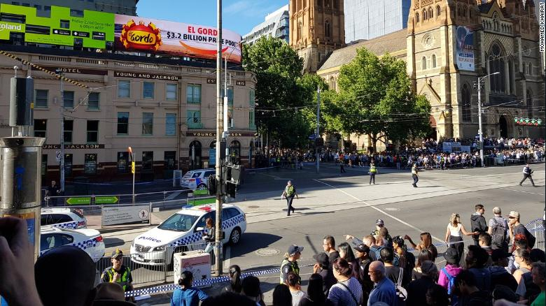 Police fence off bystanders at the pedestrian crossing next to Flinders Street Station on Thursday.