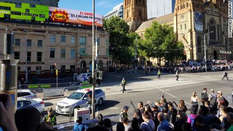 Police fence off bystanders at the pedestrian crossing next to Flinders Street Station in Melbourne, on Thursday.