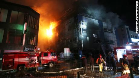 Firefighters work to extinguish a fire Thursday at an eight-story building in Jecheon, South Korea.