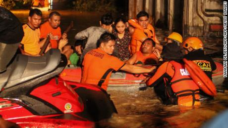 TOPSHOT - Rescue workers evacuate flood-affected residents in Davao on the southern Philippine island of Mindanao early on December 23, 2017, after Tropical Storm Tembin dumped torrential rains across the island.