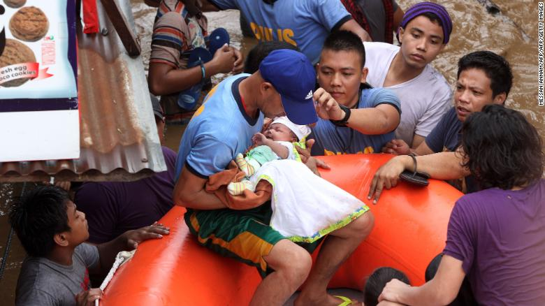 Police officers evacuate a baby in Cagayan city after Tropical Storm Tembin hit.