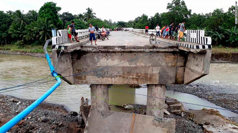 People gather on a bridge damaged by flooding from the storm Sunday in Zamboanga Del Sur in the southern Philippines.