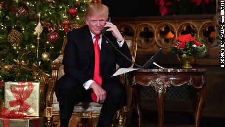 "US President Donald J. Trump participates in NORAD Santa Tracker phone calls at the Mar-a-Lago resort in Palm Beach, Florida on December 24, 2017.  ""NORAD Tracks Santa"" is an annual Christmas-themed entertainment program, which has existed since 1955, produced under the auspices of the North American Aerospace Defense Command. / AFP PHOTO / Nicholas Kamm        (Photo credit should read NICHOLAS KAMM/AFP/Getty Images)"