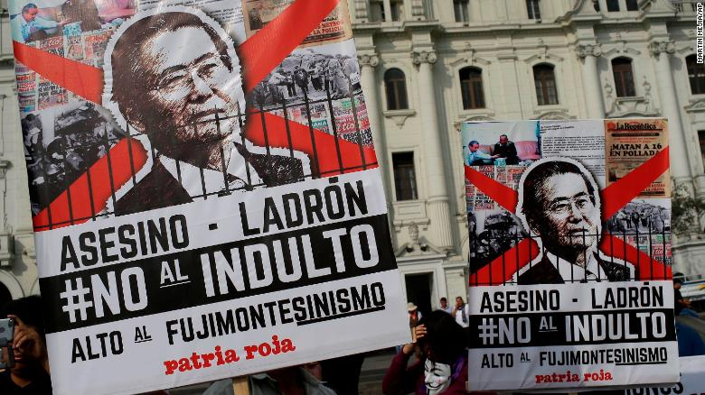 "Peruvian demonstrators protest against pardon of former President Alberto Fujimori in Lima, Peru, on Monday, with posters reading in Spanish: ""Murderer, Thief, No to pardon."""