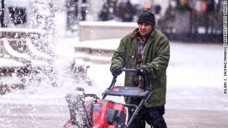 A man cleans a sidewalk with a snowplow during snowfall in Chicago on December 24.