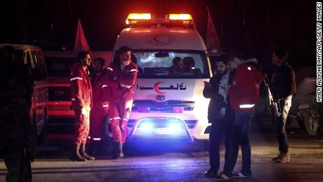 Syrian staff from the International Committee of the Red Cross take part in an evacuation operation in Douma in the eastern Ghouta region on the outskirts of the capital Damascus late on December 26, 2017.