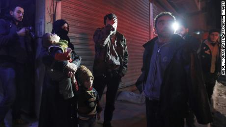 Syrian civilians wait during an evacuation operation in Eastern Ghouta on Tuesday.