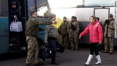 The first Ukrainian prisoners get off a bus Wednesday during a prisoner exchange at a checkpoint near the eastern Ukraine city of Horlivka.