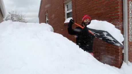 Patrick Harden clears snow from the roof of his car on Tuesday, Dec. 26, 2017, in Erie, Pa. The National Weather Service office in Cleveland says Monday's storm brought 34 inches of snow, an all-time daily snowfall record for Erie. Another 19 inches fell before dawn Tuesday, making the greatest two-day total in commonwealth history. (Greg Wohlford/Erie Times-News via AP)