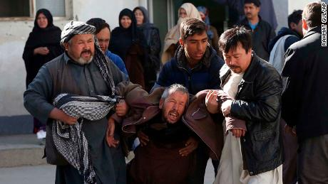 A distraught man is carried away following the suicide attack in Kabul on Thursday.