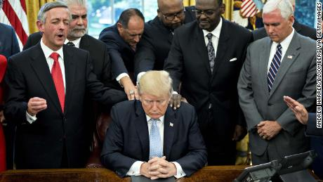U.S. President Trump, center, bows his head during a prayer while surrounded by U.S. Vice President Mike Pence, right, faith leaders and evangelical ministers after signing a proclamation declaring a day of prayer in the Oval Office of the White House in Washington, D.C., U.S., on Friday, Sept. 1, 2017. Trump declared Sunday, September 3 a national day of prayer for Hurricane Harvey victims. Photographer: Andrew Harrer/Bloomberg via Getty Images
