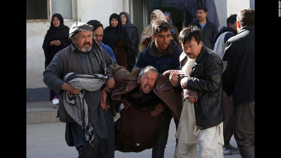 A man is carried away from a suicide attack in Kabul, Afghanistan, on December 28. A suicide bomber detonated explosives in the meeting room of a Shiite cultural center. The blast killed at least 40 people.