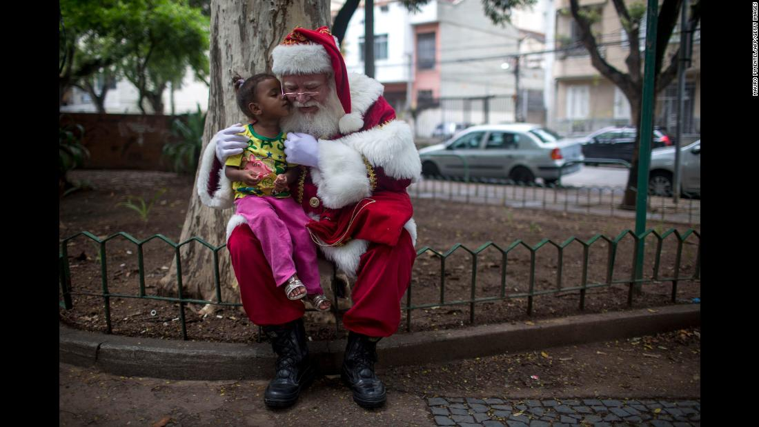 A man dressed as Santa Claus poses for pictures with a girl on December 26 in Rio de Janeiro.