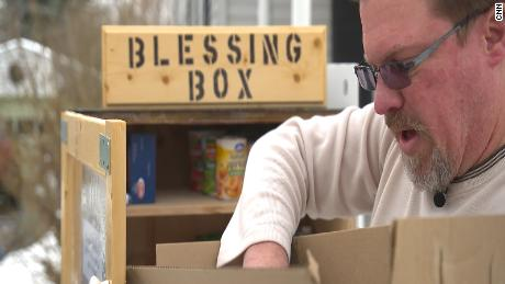 Chris Damm, a Watertown, New York resident, fills up the blessing box on his lawn with donated goods.