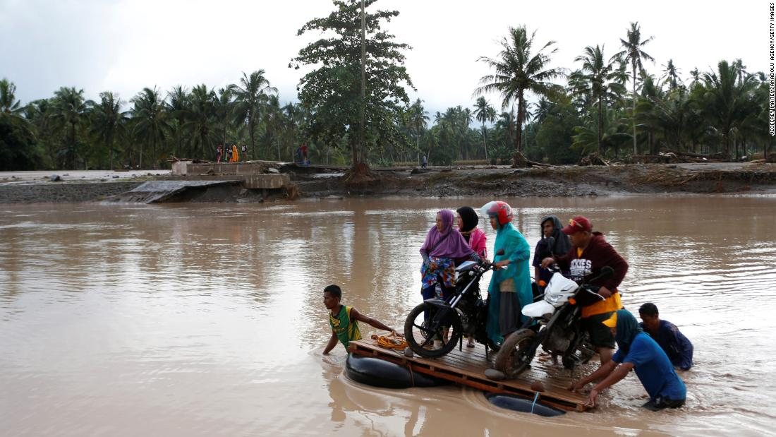 People cross a river on makeshift rafts in the flood-hit town of Salvador, Philippines, on December 23.