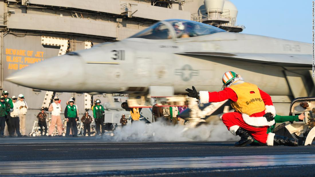 Lt. Larry Young, dressed as Santa, signals to launch an F/A-18E Super Hornet on the flight deck of the aircraft carrier USS Theodore Roosevelt.
