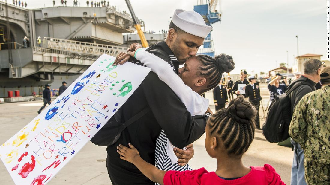 Navy Petty Officer 1st Class Corey Oliver hugs his daughter in San Diego on December 5, following a regularly scheduled deployment aboard the USS Nimitz to the Western Pacific.