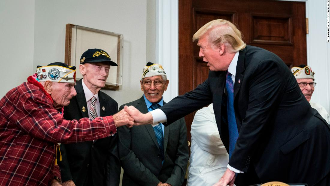 President Donald Trump greets World War II veteran Lawrence Parry before signing a proclamation for National Pearl Harbor Remembrance Day with survivors of the attack.