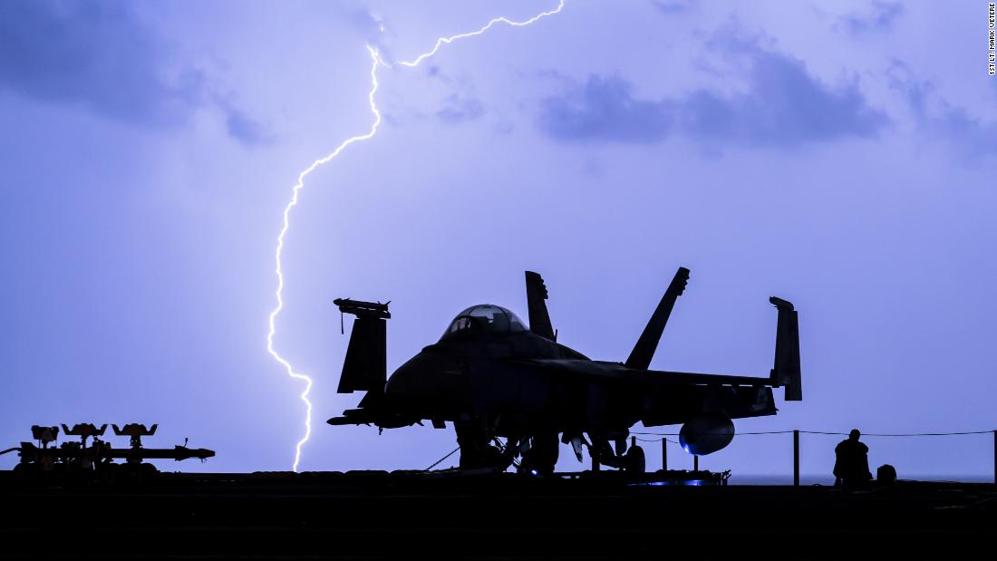 Lightning strikes near the aircraft carrier USS Theodore Roosevelt as it travels in the Persian Gulf on December 16.