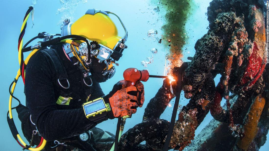 Navy Petty Officer 2nd Class Chris Carlson performs underwater cutting operations while working with divers assigned to Underwater Construction Team 2 in Apra Harbor, Guam, on December 11.