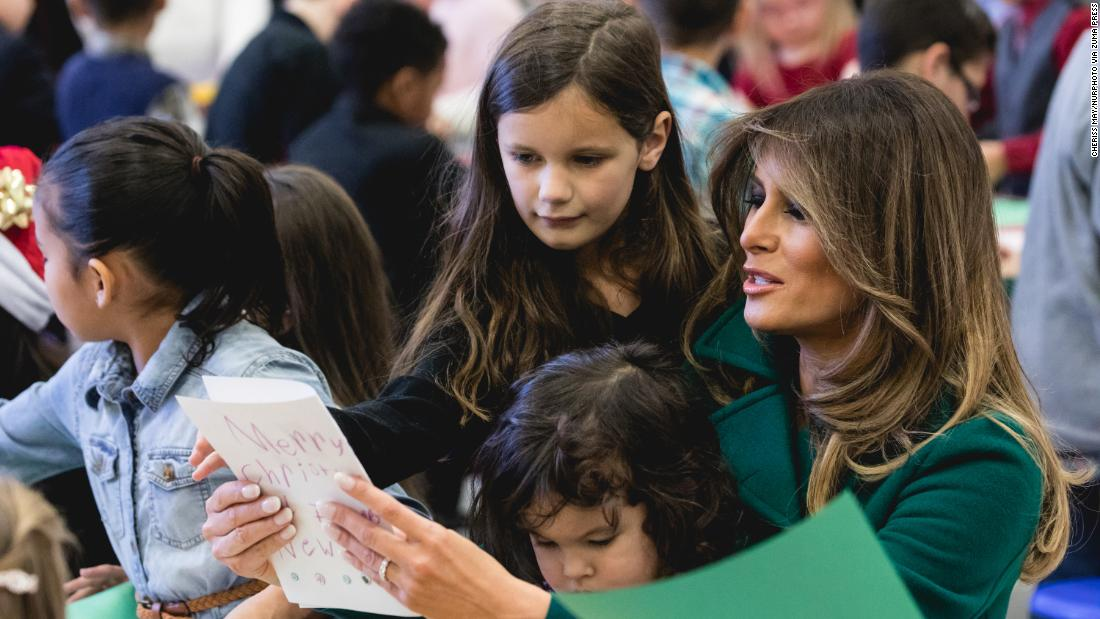 First Lady Melania Trump sits with 3-year-old Mehreem Donahue in her lap, as she makes Christmas cards with military kids at the Marine Corps' annual Toys for Tots event on December 13.
