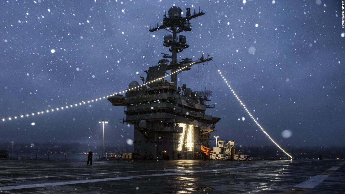A sailor walks across the flight deck of the aircraft carrier USS John C. Stennis after being relieved from watch while the ship is port in Bremerton, Washington, on December 25, preparing for its next deployment.