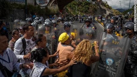 A group of protesters gather in front of members of the Bolivarian National Police in Caracas, Venezuela, on Thursday.