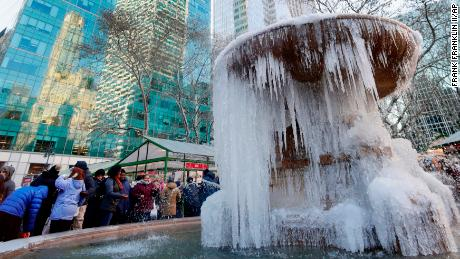 People pose for photographs in front of a frozen water fountain at Bryant Park, Thursday, Dec. 28, 2017, in New York. A large swath of northern New York is encased in ice and snow after days of lake-effect storms followed by an arctic cold front sending temperatures well below zero. (AP Photo/Frank Franklin II)