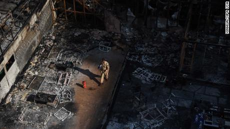 A policeman walks through the burned building on Friday morning.