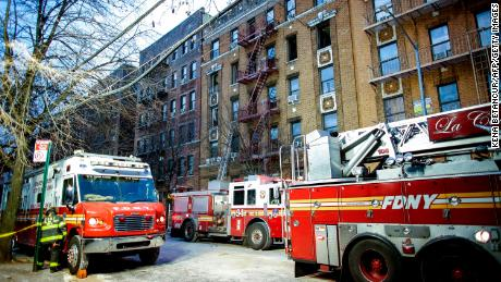 Fire Department of New York personnel work at the scene of an apartment fire in the Bronx borough of New York City on December 29, 2017.