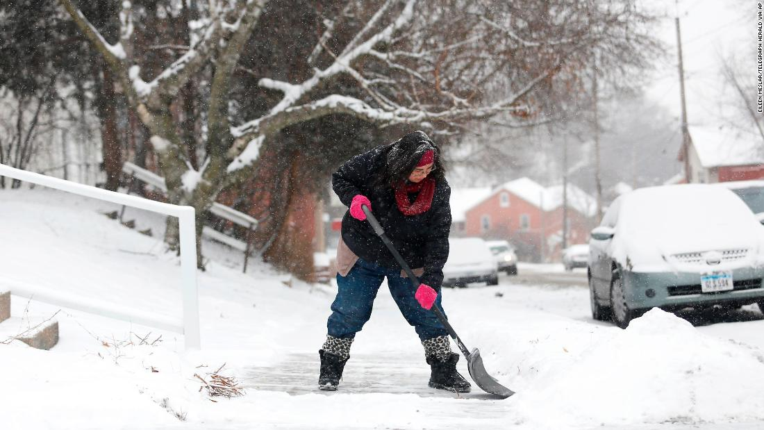Samantha Dement-Graham shovels her neighbor's sidewalk in Dubuque, Iowa, on Friday, December 29.