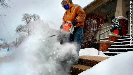 Jose Nieto uses a leaf blower to clear snow from the steps of a sick neighbor during a snowstorm, Friday, Dec. 29, 2017, in Bloomington, Ill. A snow mask and hearing protection allowed him to do his driveway and sidewalks as well. (David Proeber/The Pantagraph via AP)