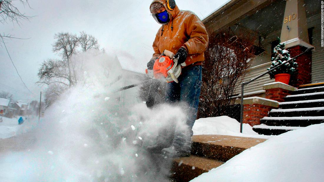Jose Nieto uses a leaf blower to clear snow from the steps of a sick neighbor's house in Bloomington, Illinois, on December 29.