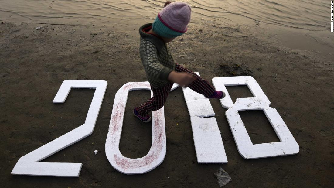 "A child walks on numbers reading ""2018"" in Allahabad, India."