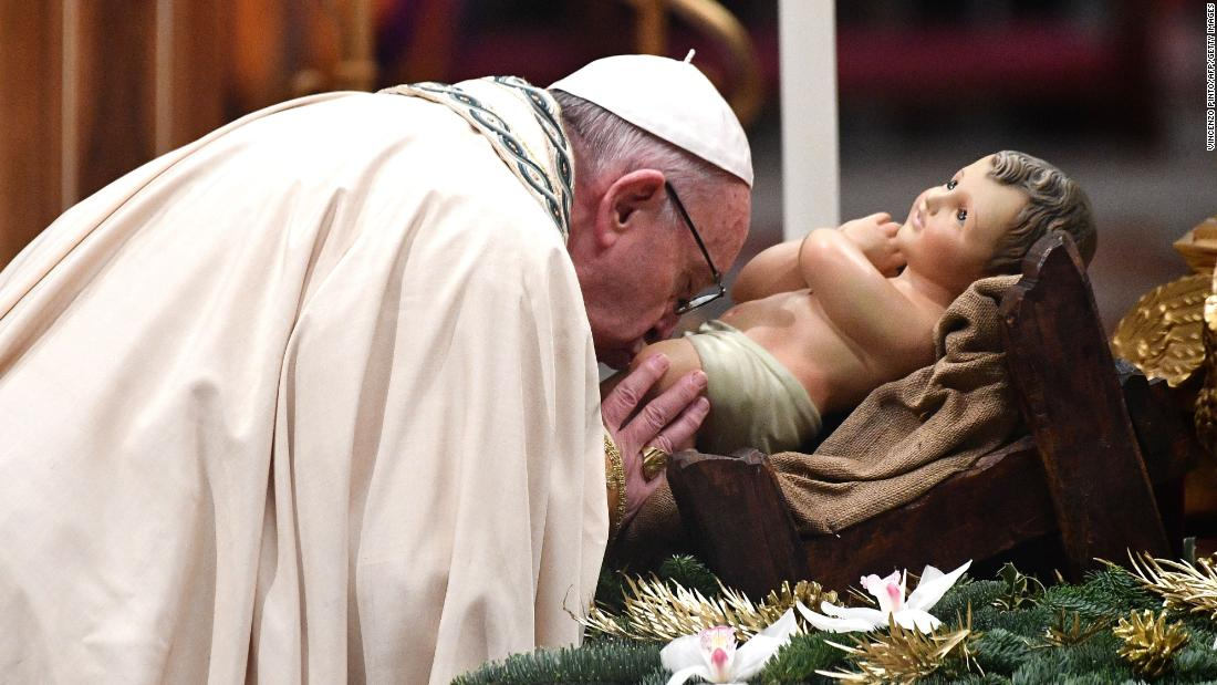 Pope Francis kisses the Christ Child upon his arrival to preside over the Te Deum prayer in St, Peter's Basilica at the Vatican.